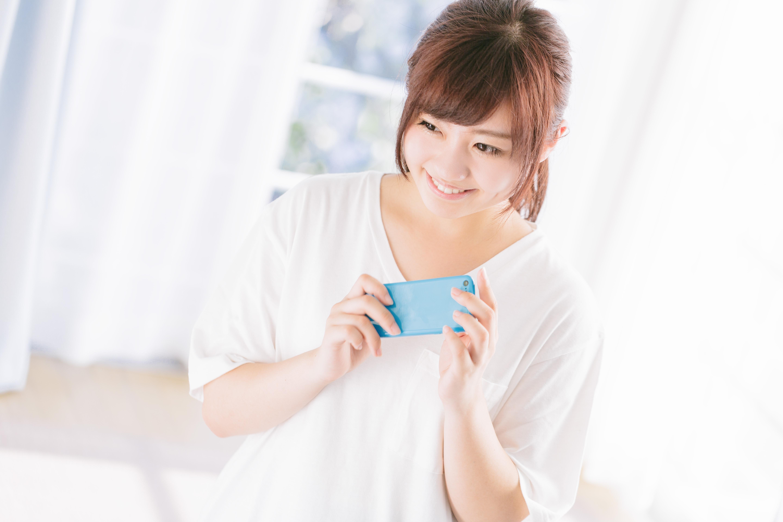 スマホを持って嬉しそうに微笑む女性