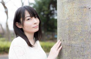 木に手を置きこちらを見てほほ笑む女子