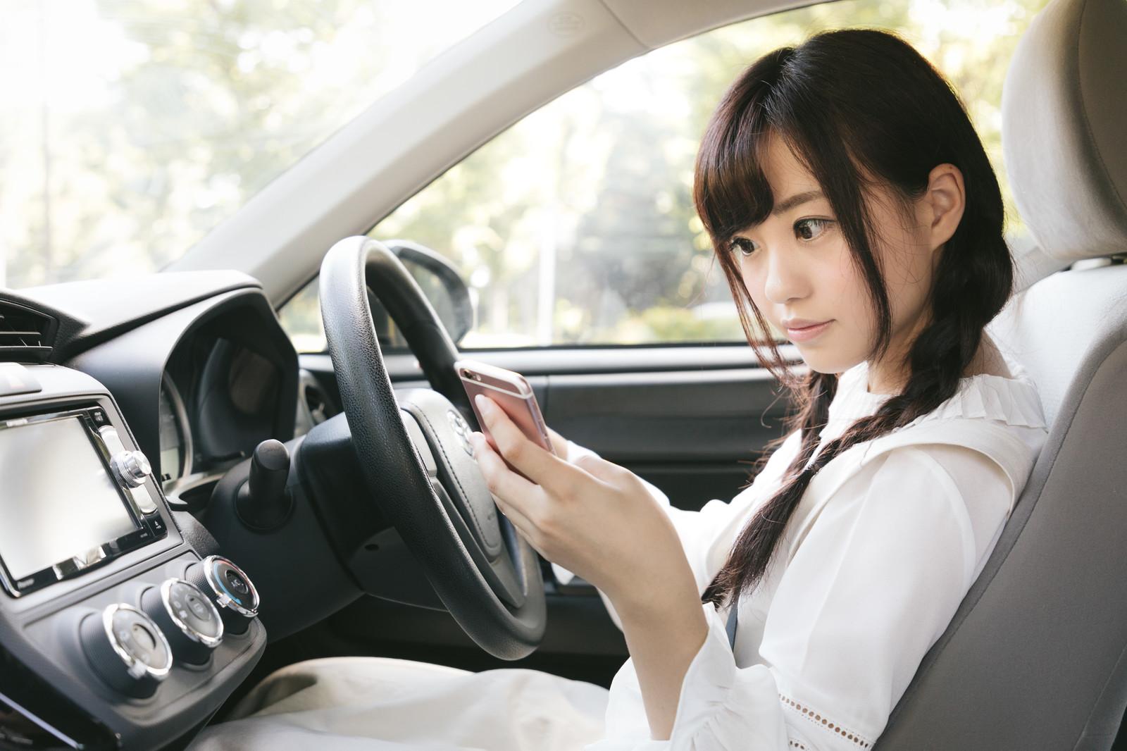 車でスマホを見ている女性